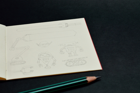 Square sketchbook with handmade drawings of robots, pencil line style. Archivio Fotografico - 121015673