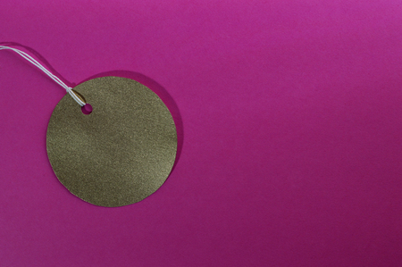 Template of gold paper tag on pink background.