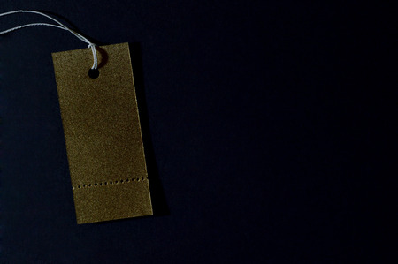 Template of gold paper tag on dark background.