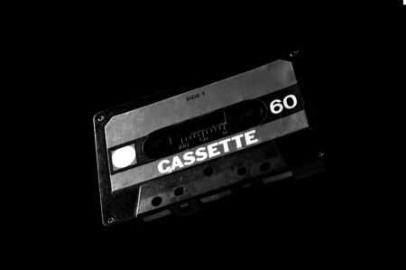 Black and white template of old audio cassette on dark background.