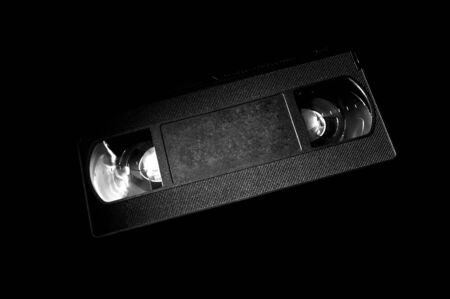 Black and white template of old video cassette on dark background.