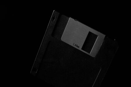 Black and white template of old diskette on dark background.