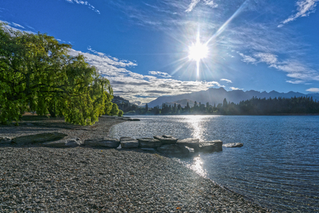 Lake Wakatipu with mountian peaks in the background on a sunny morning.