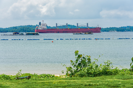 Singapore - July 8, 2018: Bulk carrier in Johor Strait in front of Pulau Ubin. Editorial