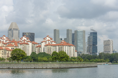 Singapore  - June 18, 2018: Condominiums by the river  and downtown skyscrapers in the back Editorial