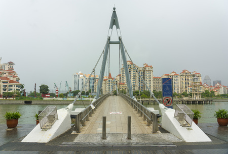 Singapore  - June 18, 2018: Tanjong Rhu Suspension Bridge in front of Tanjong Rhu with condominiums