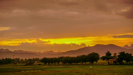 Mountains, trees, nature evening sky at sunset because of the beautiful yellow. Stock Photo