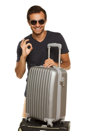 Young tanned male in sunglasses standing with silver travel suitcase,  showing OK sign, isolated on white background photo