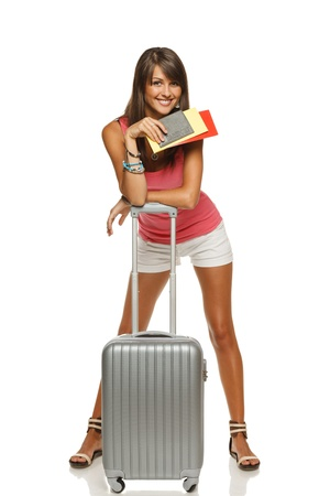 Full length of young female in casual leaning on the travel bag, holding passport and tickets, ready to leave for vacations, isolated on white background photo