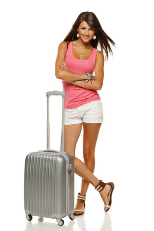 Full length portrait of young female standing with suitcase going on holidays isolated on white background photo