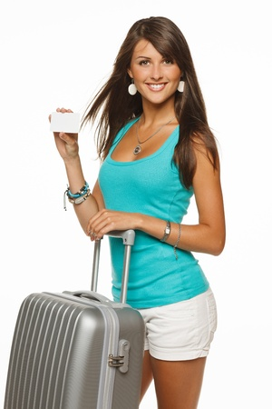 Young woman in casual standing with silver travel bag holding empty credit card, isolated on white background photo