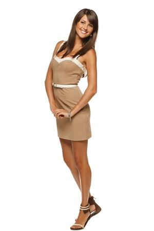 Full length portrait of trendy young woman in elegant beige dress posing against white background photo