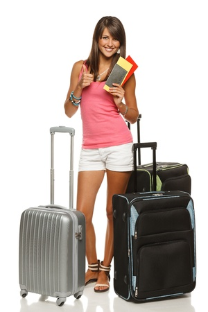 Full length of young female in casual standing with travel bags, holding passport and tickets, showing thumb up sign, isolated on white background Stock Photo - 15009794