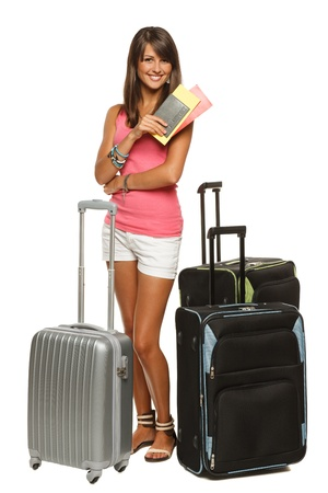 Full length of young female in casual standing with travel bags, holding passport and tickets, isolated on white background photo