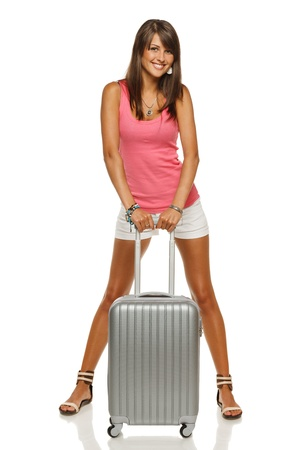 Full length portrait of young female standing with silver suitcase going on holidays isolated on white background photo