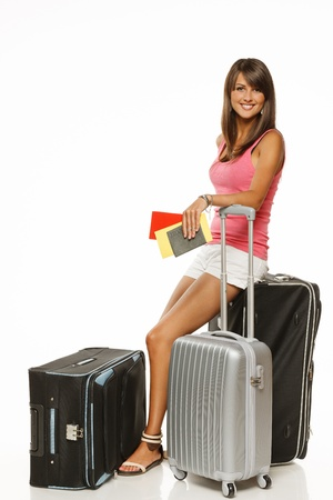 Full length of young female in casual sitting on her travel bags and holding the tickets with passport isolated on white background Stock Photo - 15009789