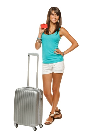 Full length of young woman in casual standing with silver travel bag holding empty credit card, isolated on white background Stock Photo