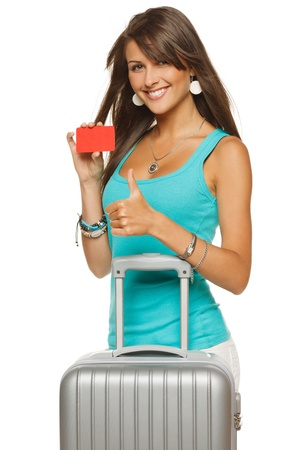 travel bag: Young woman in casual standing with silver travel bag holding empty credit card and showing thumb up sign, isolated on white background
