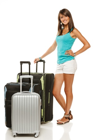 Full length portrait of young female standing with three suitcases going on holidays isolated on white background photo