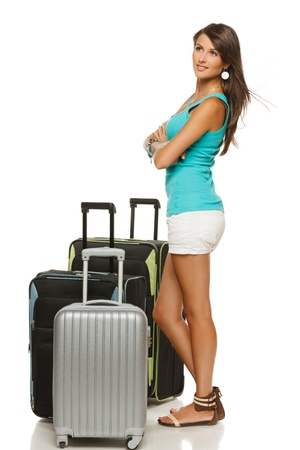 sideways: Full length portrait of young female standing with three suitcases going on holidays, looking sideways, isolated on white background
