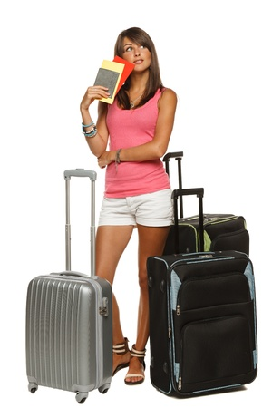 Full length of young female in casual standing with travel bags, holding passport and tickets, looking up, isolated on white background