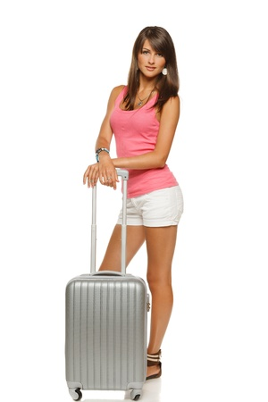 tank top: Full length portrait of young female standing with silver suitcase going on holidays isolated on white background