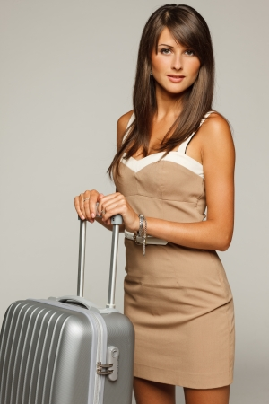 Portrait of trendy young woman in elegant beige dress standing with silver travel bag Stock Photo - 15009811