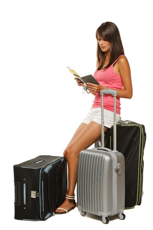 Full length of young female in casual sitting on her travel bags and checking the tickets isolated on white background