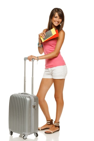 Full length of young female in casual standing with travel bag, holding passport and tickets, isolated on white background photo