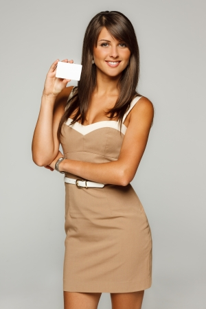 Portrait of young smiling business woman in beige dress holding empty credit card isolated on gray background photo