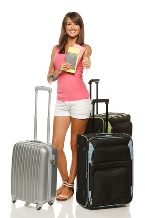 Full length of young female in casual standing with travel bags, holding passport and tickets, showing thumb up sign, isolated on white background photo