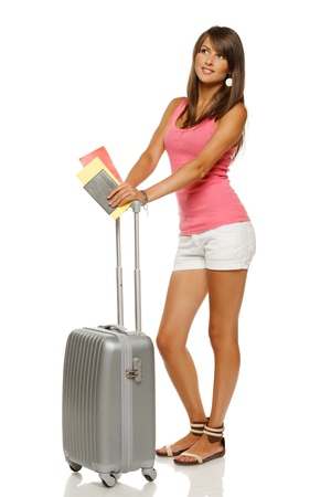 Full length of young female in casual standing with travel suitcase, holding passport and tickets, looking away, isolated on white background photo