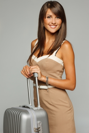 Portrait of trendy businesswoman in elegant beige dress standing with silver travel suitcase photo