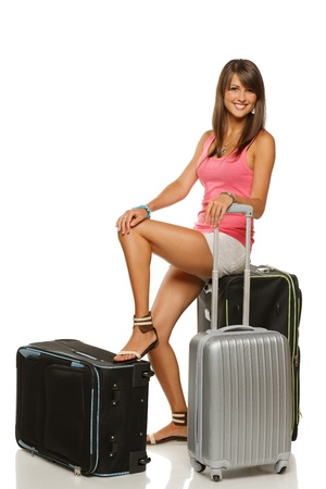 Full length of young smiling female in casual sitting on her travel suitcases, isolated on white background Stock Photo - 15009778