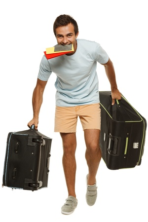 Young male tourist hurrying to the flight holding tickets with passport in his teeth, isolated on white background photo