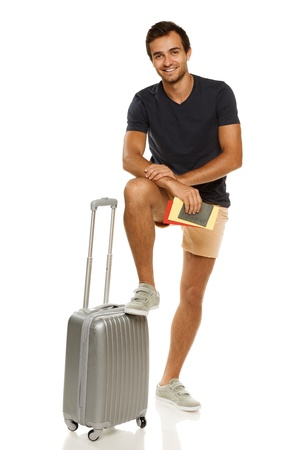 Full length of young male standing with silver suitcase, holding tickets and passport, with his leg on the suitcase, isolated on white background photo