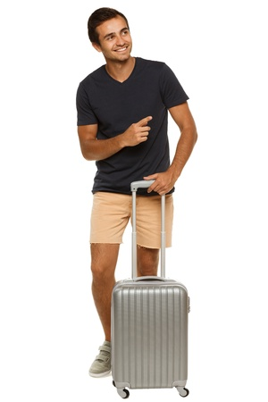 sideways: Full length of young male tourist standing with silver suitcase, pointing to the side, isolated on white background