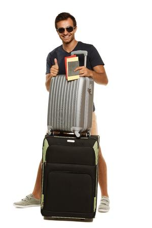 viajero: Longitud total de j�venes de pie bronceado masculino con maletas, billetes de las explotaciones y los pasaportes, que muestra el pulgar hacia arriba signo aislado sobre fondo blanco