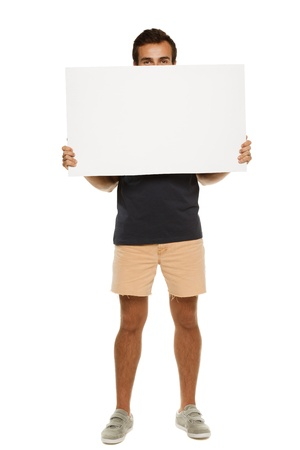 Full length young man in summer casual clothing peeking from the blank banner, over white background photo