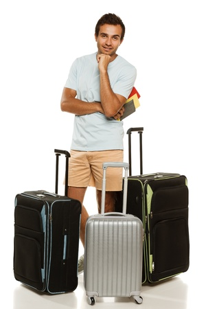 traveller: Full length of young man standing with three travel suitcase, holding passport with tickets, against white background