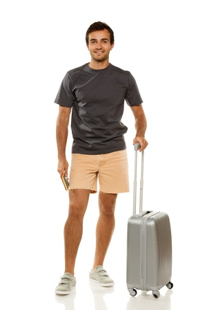 explorer man: Full length of young male tourist standing with suitcase, holding tickets and passport, isolated on white background
