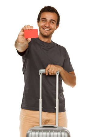 Young smiling male with suitcase showing empty credit card  Shallow depth of field, focus on credit card  photo