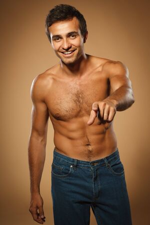 Young smiling male shirtless pointing at you, over beige background photo