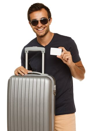 Handsome tanned smiling male in sunglasses standing with suitcase and holding empty credit card, over white background photo