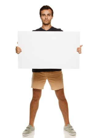 board shorts: Full length of young man in summer casual clothing holding blank banner, over white background
