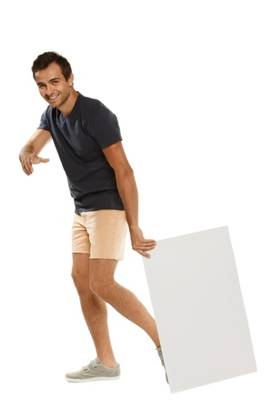 Full length of young man in summer casual clothing pulling blank banner along and pointing at you, over white background Stock Photo - 15063137