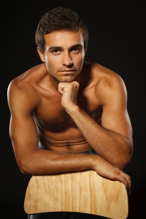 stubble: Young muscular male shirtless leaning on the chair, over black background Stock Photo