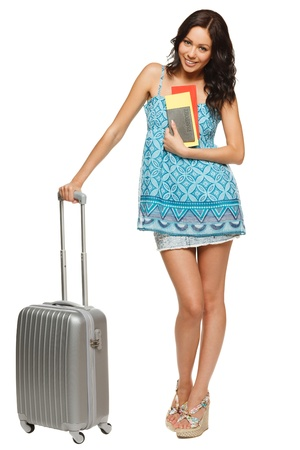 withe background: Full length of young female in casual standing with travel bag, holding passport and tickets,isolated on withe background