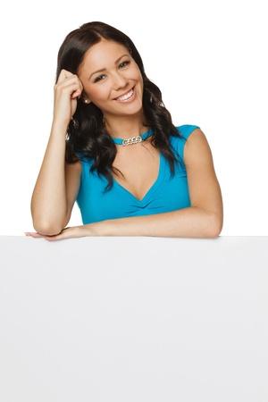elleboog: Lachende gelukkige vrouw achter en leunend op een witte lege billboard aanplakbiljet, over witte achtergrond
