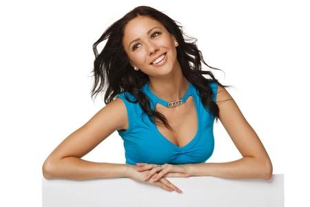 elleboog: Lachende gelukkige vrouw achter en leunend op een witte lege billboard aanplakbiljet, op zoek naar de kant, over witte achtergrond